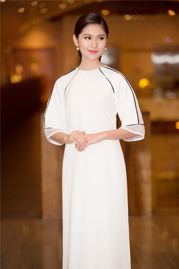 Á hậu Thùy Dung thanh lịch với áo dài trắng được nhấn nhá bằng những đường viền đen tương phản. Thiết kế được cách điệu bằng những đường cắt, cách dựng phom ở cổ và tay áo.