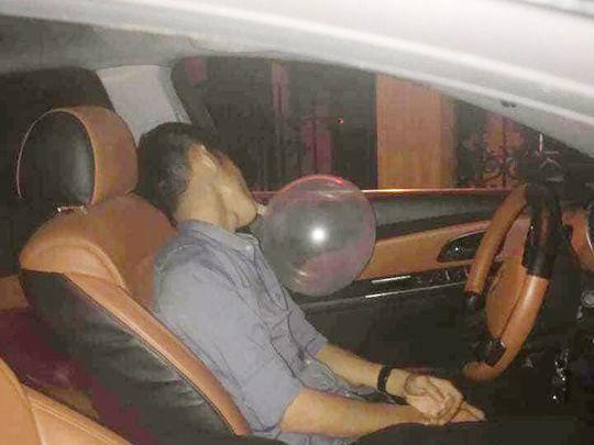 Hình ảnh tài xế miệng ngậm một quả bóng trong xe mở nhạc rất to.