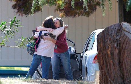 2 phụ nữ an ủi nhau phía ngoài ngôi trường nơi nghi phạm ra tay. Ảnh: AP.