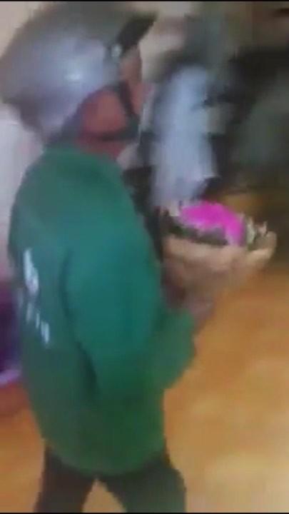 Chú công nhân vội vã mang hoa vào nhà khi đầu vẫn còn đội mũ bảo hiểm