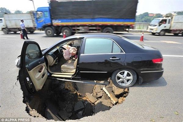 """""""Ổ khủng long"""" trên đường phố Trung Quốc hồi tháng 6/2010. Chẳng hiểu sao người tài xế có thể thoát nạn được trong trường hợp này."""