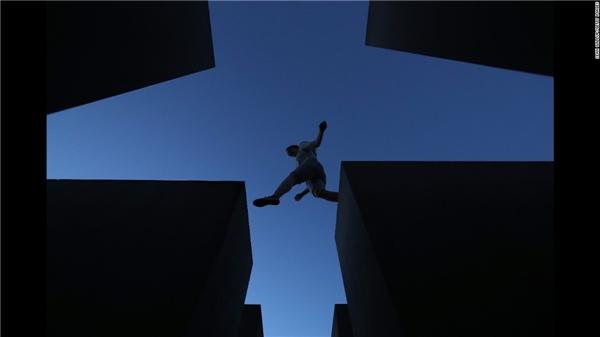 Berlin:Một khách tham quan đang bước qua những tòa nhà trong 2711 tòa nhà bê tông của quần thể Đài Tưởng Niệm Diệt Chủng ở Berlin.