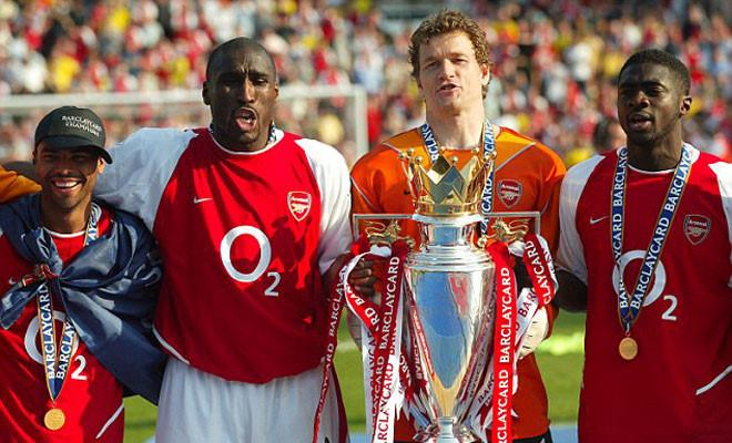 """Là nhân tố không thể thiếu nơi khung gỗ của đội hình vĩ đại bậc nhất trong lịch sử của """"The Gunners"""". Jens Lehmann đã để lại những dấu ấn đặc biệt tại sân Highbury ngay trong mùa giải đầu tiên đặt chân đến thành London. Với 47 trận đấu bất bại ở đấu trường Ngoại hạng Anh (38 trận ở mùa giải 2003/04, 9 trận ở mùa giải 2004/05), Jens Lehmann chính là ngôi sao sở hữu số trận bất bại dài nhất hiện tại của nền bóng đá xứ sở sương mù. Với sự cạnh tranh mạnh mẽ ở thời điểm hiện tại, kỷ lục của thủ thành người Đức nhiều khả năng sẽ còn tồn tại một thời gian dài nữa tại Ngoại hạng Anh."""