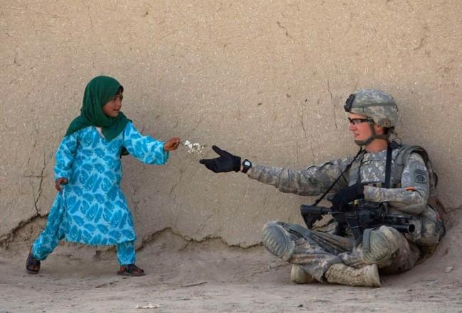 """Giữa chiến tranh bom đạn, một đứa trẻ thơ ngây tạiAfghanistanvẫn rất vô tư như thế. Cành hoa em bé tặng cho anh lính Mỹ như muốn nói """"Chỉ mong thế giới này hòabình thôi chú nhỉ""""."""