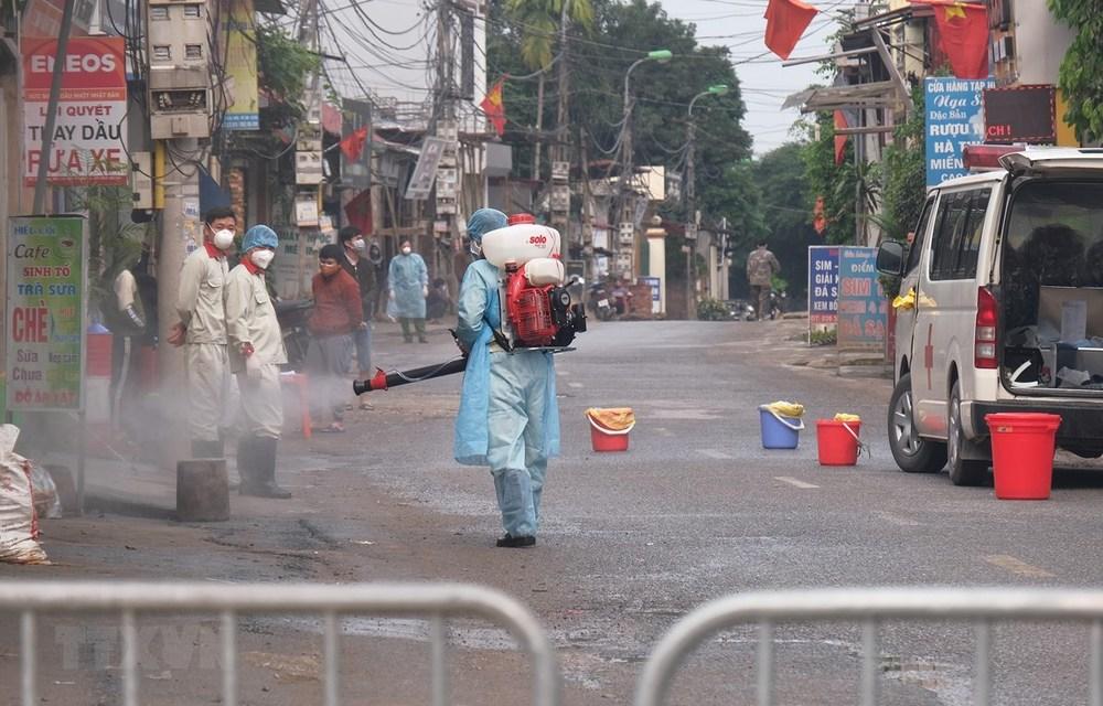 Nhân viên y tế phun khử trùng ở thôn Hạ Lôi, Mê Linh (Ảnh: TTXVN)