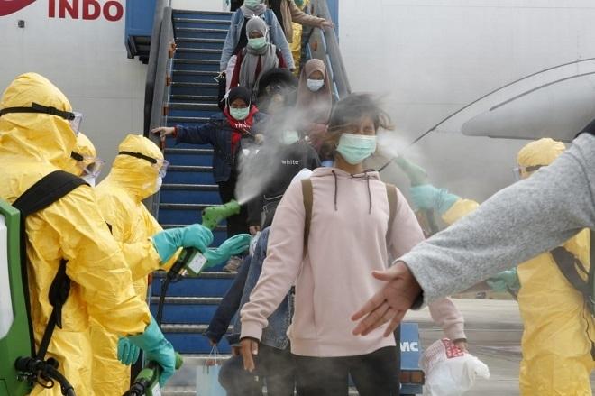 Người trở về từ vùng dịch được phun khử trùng ngay sau khi xuống máy bay (Ảnh: Vnexpress)