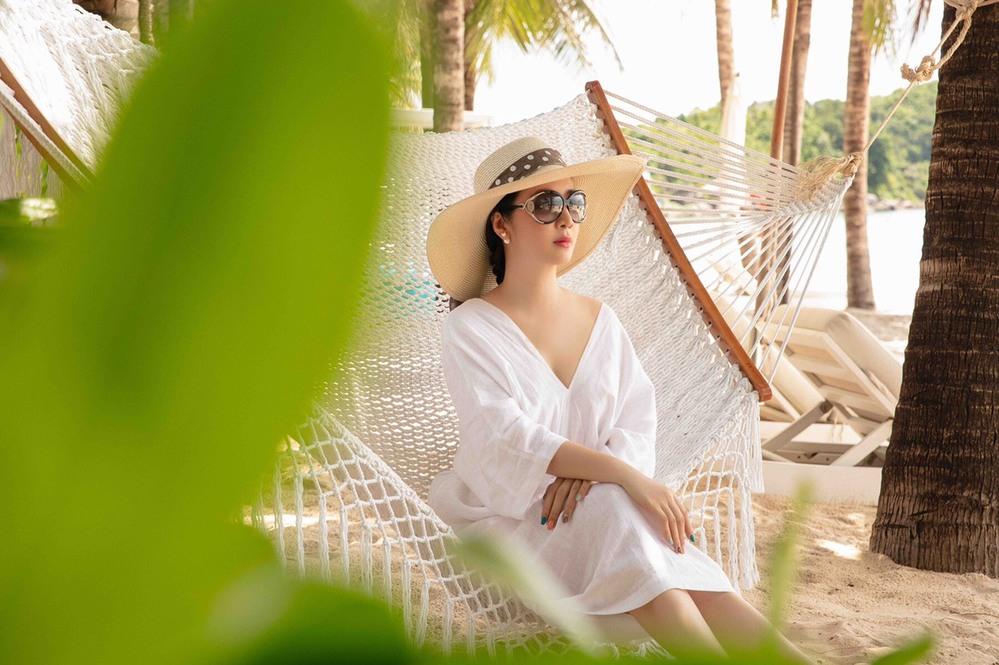 Giáng My dù ở đâu cũng thần thái sang chảnh, Hoa hậu Đền Hùng chọn váy trễ vai dáng suông, đội nón cói và đeo mắt kính đen bản lớn cho buổi đi biển hôm nay. (Ảnh: FBNV)