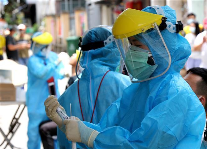 Nhân viên y tế đang tiến hành lấy mẫu xét nghiệm nCoV. (Ảnh: Báo Tin Tức)