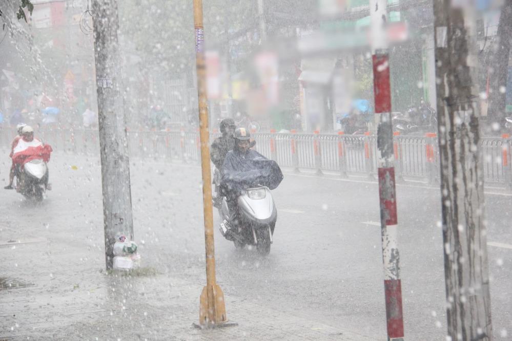 Hình ảnh mọi người di chuyển ngoài đường trong cơn mưa lớn. (Ảnh: Thanh Niên)