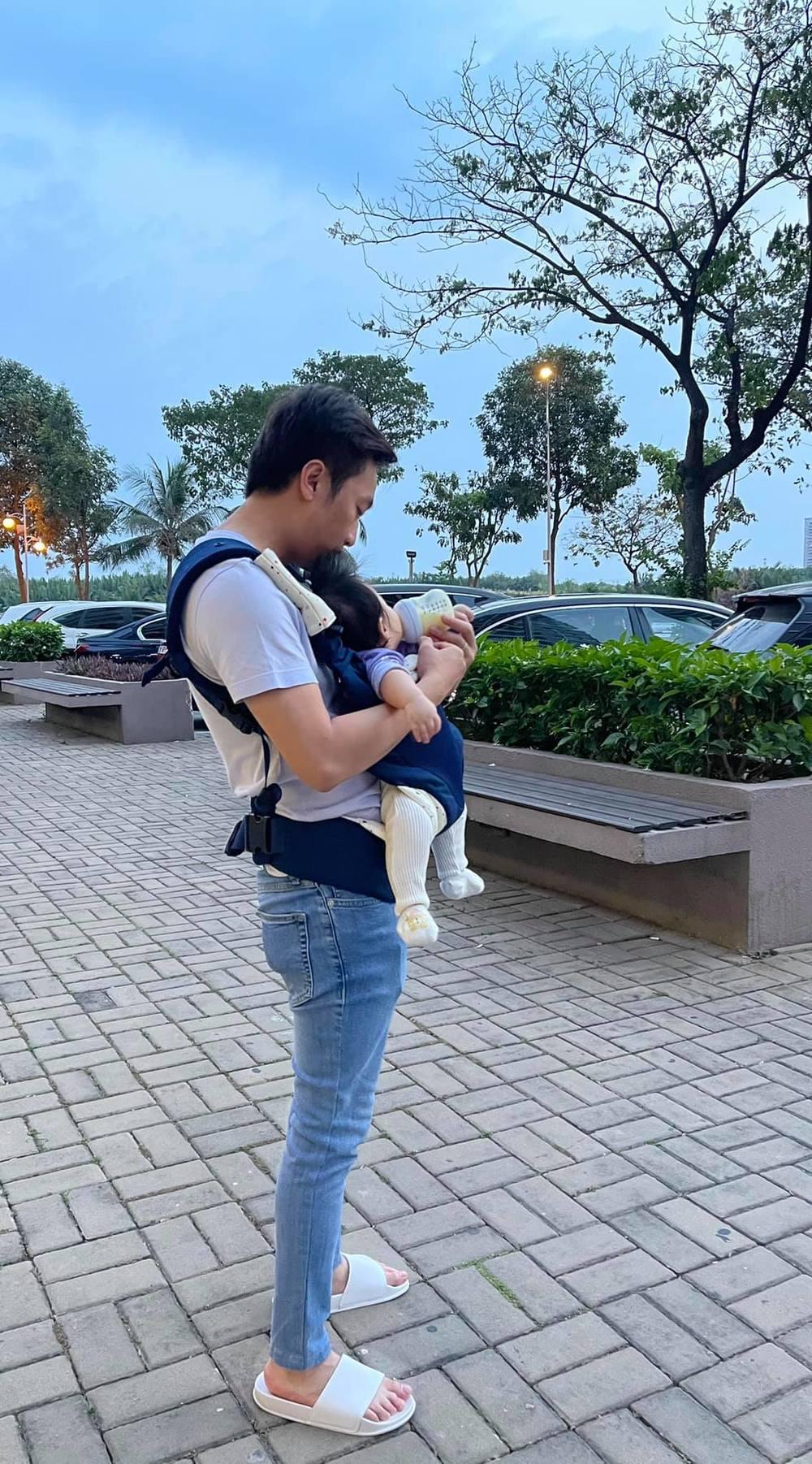 """Diện trang phục chỉn chu ra đường nhưng """"ông bố 2 con"""" vẫn không quên nhiệm vụ địu công chúa trên vai để cho uống sữa và ngắm mọi thứ xung quanh. (Ảnh: FBNV) - Tin sao Viet - Tin tuc sao Viet - Scandal sao Viet - Tin tuc cua Sao - Tin cua Sao"""
