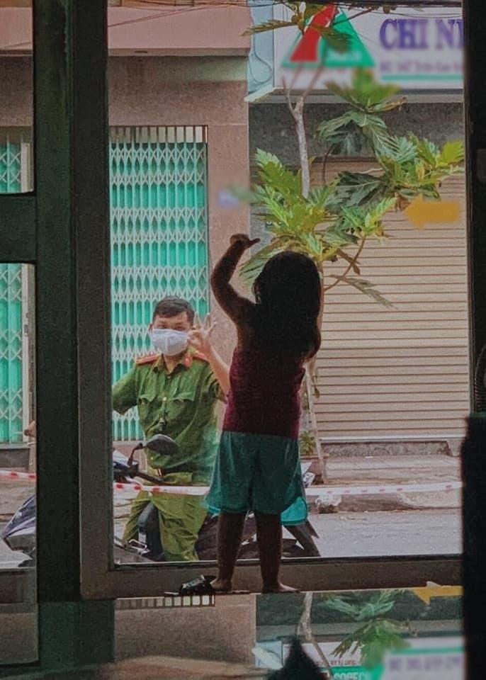 Bố và con gái chào nhau qua cánh cửa kính.(Ảnh: Chụp màn hình)
